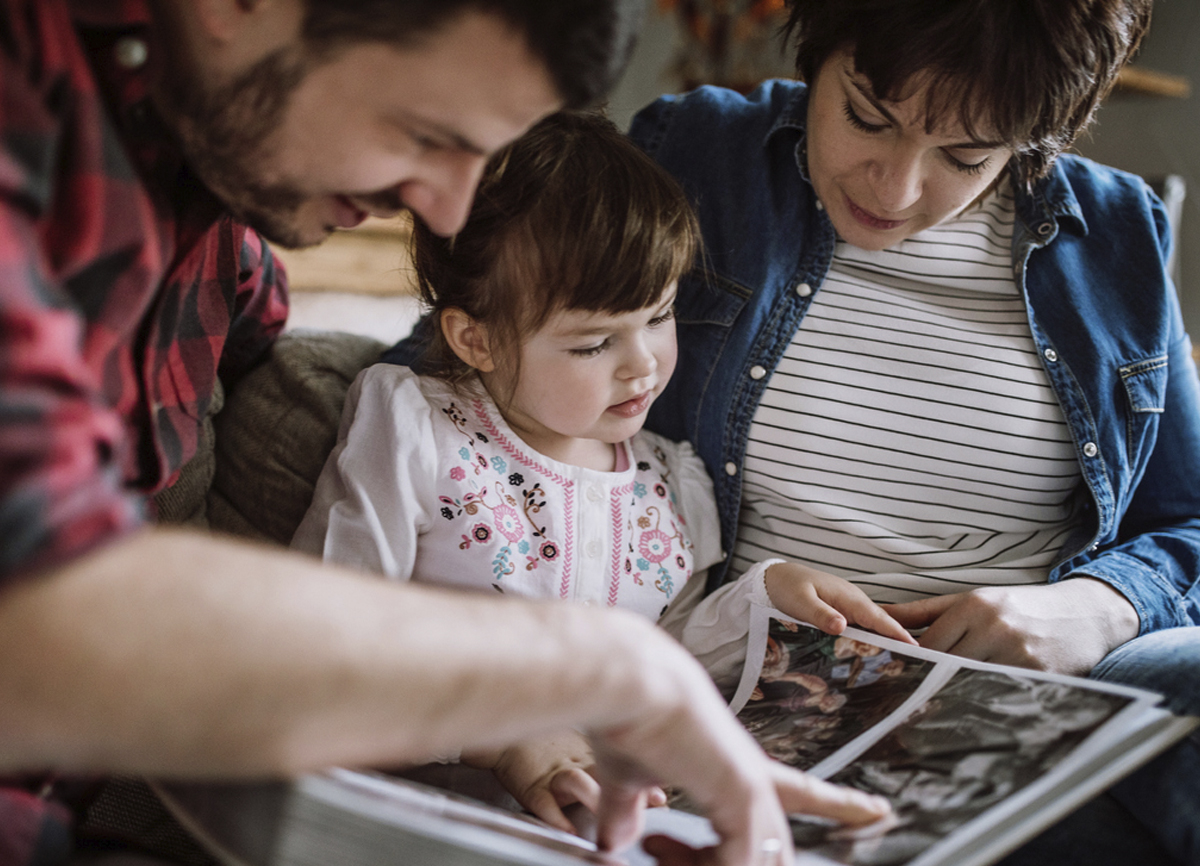 A couple flipping through a photo album with their young daughter.