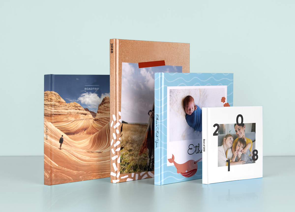 four photo books in a mixture of sizes and formats, ranging from baby books to travel books.
