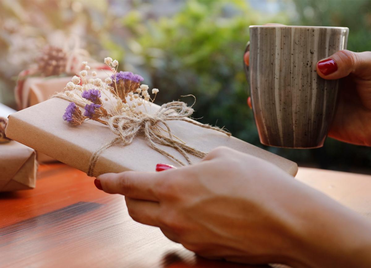 En hand håller en bok som är inslagen i brunt presentpapper och omlindat med ett snöre med små lila och vita blommor fästa vid det.